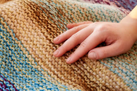 The woman's hand lies on knitted multicolored woolen handmade plaid, close-up, creative background. Banco de Imagens
