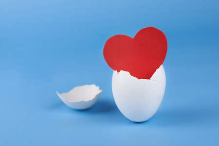 Paper red heart in an eggshell on a blue background, the concept of the birth of a new life and love.