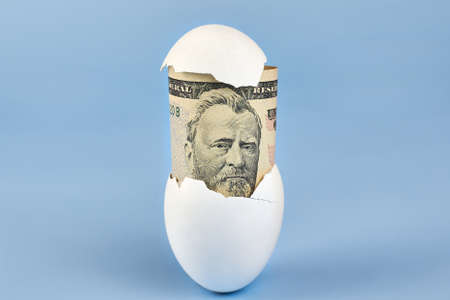 American fifty dollar bill from eggshell on blue background, earnings concept. Banco de Imagens