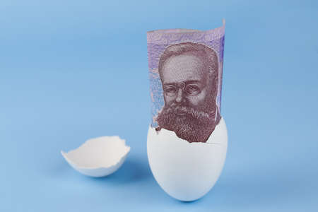 Ukrainian fifty hryvnia banknote from eggshell on blue background, earnings concept.