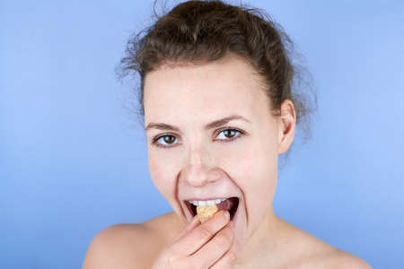 Beautiful smiling woman doing facial exercises with wine crusts, face fitness, self-massage against wrinkles and old age, care for the beauty of the skin.
