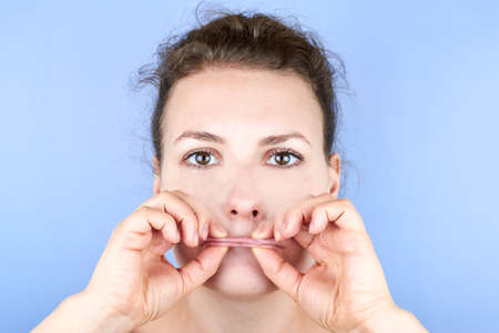 Beautiful woman doing facial exercises, face fitness, self-massage against wrinkles and old age, care for the beauty of the skin.
