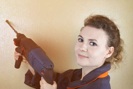 Smiling beautiful woman in workwear with a puncher near the wall. Banco de Imagens