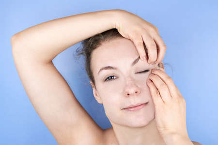 Beautiful smiling woman doing facial exercises, face fitness, self-massage against wrinkles and old age, care for the beauty of the skin.