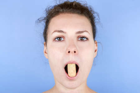 Beautiful woman doing facial exercises with wine crusts, face fitness, self-massage against wrinkles and old age, care for the beauty of the skin.
