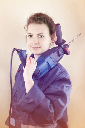 Smiling beautiful woman in workwear with a puncher near the wall, toned photo.