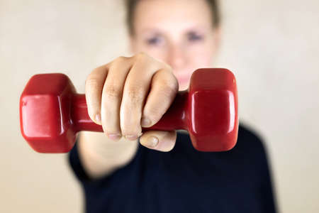 Woman holding a dumbbell in front of herself, workout at home. Banco de Imagens