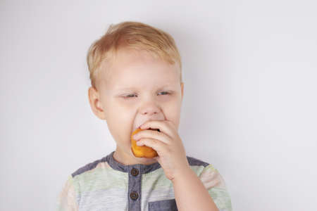 Three-year-old funny boy eats a pie on a white background.