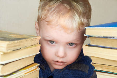 A small three-year-old funny boy looks out from a stack of books.