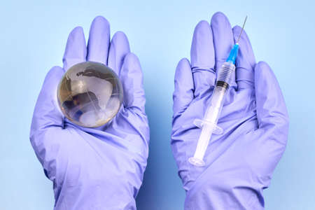 Woman's hands in medical gloves is holding a planet earth globe and a syringe, the concept of vaccination.