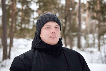 Portrait of a young man in a hat and jacket in the winter forest.