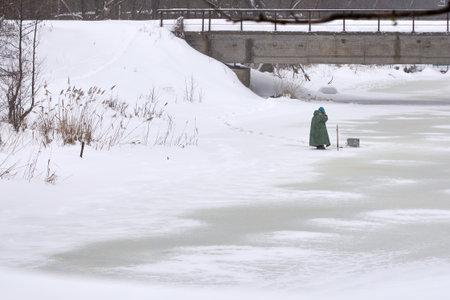 A fisherman speaks on the phone on a frozen river under a bridge, winter fishing.