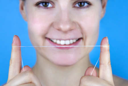 Smiling woman holding dental floss in front of her on a blue background.