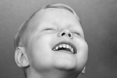 Portrait of a three-year-old smiling boy, black and white photo.