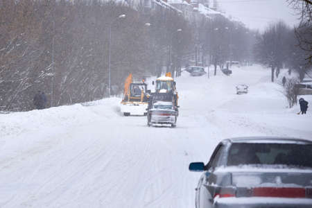 A tractor cleans snow on the road during a blizzard in winter, snow removal equipment. Banco de Imagens
