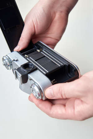 Retro photo camera in the hands of a man on a white background.