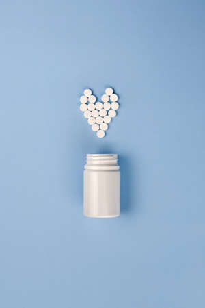Blue pills poured from the jar in the shape of a heart on a blue background, the theme of diseases.