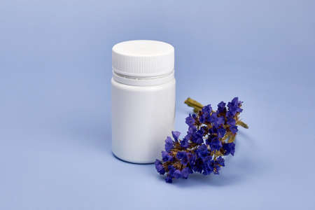 Dried flower near a jar of pills, herbal medicines, homeopathic concept. Banco de Imagens