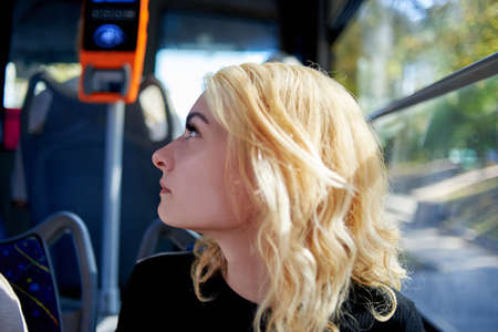 Portrait of a beautiful young woman who rides in a trolleybus near the window.