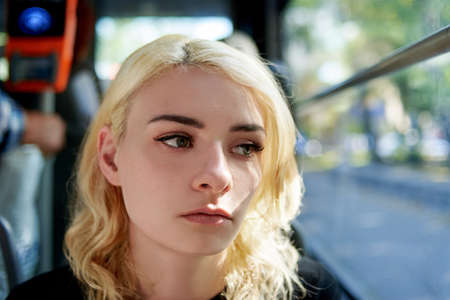 Portrait of a sad beautiful young woman who rides in a trolleybus and looks out the window.