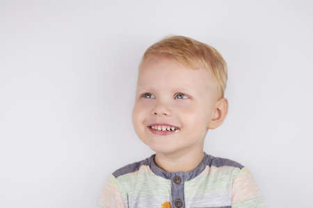 Three-year-old smiling funny boy with a mouth smeared with cake crumbs on a white background.
