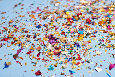 Bright colorful confetti sparkles on a blue background, the theme of a holiday and a birthday.
