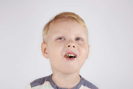 Three-year-old funny boy with a mouth smeared with cake crumbs on a white background.