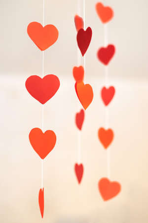 Paper red decorative hearts hang on a thread, Valentine's Day concept. Banco de Imagens