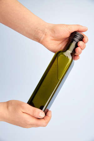 Green transparent glass bottle of olive oil in the hands of a woman on a light background. Banco de Imagens