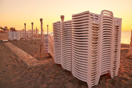 Folded sun loungers and umbrellas on the sea beach at sunrise, preparation for a new day. 免版税图像