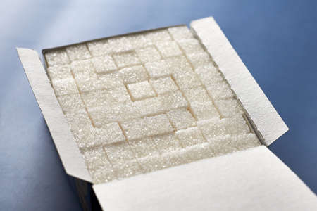 White sugar cubes in a paper box on a blue background. 免版税图像