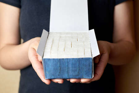 White sugar cubes in a paper box in the hands of a woman.