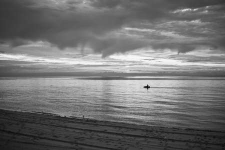 A man is sailing in an inflatable boat on the sea, black and white photo. 免版税图像