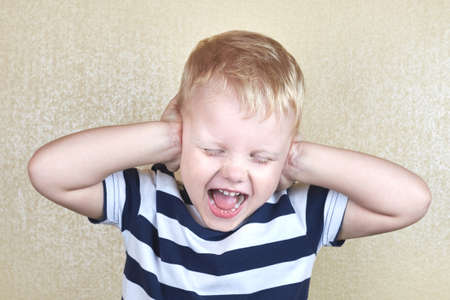 Little boy in a striped T-shirt covered his ears with his hands and screaming.