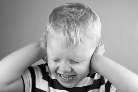 Little boy covered his ears with his hands and screaming, black and white photo. 免版税图像