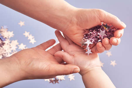 Woman lays down in the child's hand pink shiny stars confetti on a blue background, Christmas and celebration concept. 免版税图像