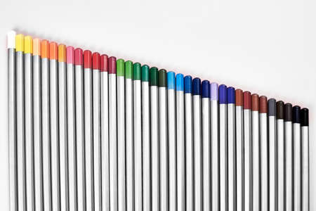 Colored pencils lined up in a row on a pink background, the theme of creativity and hobby.
