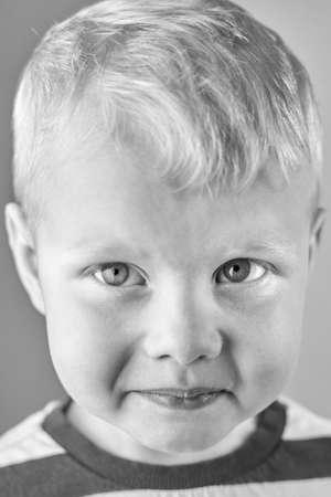 Portrait of a little sad lonely caucasian boy, black and white photo. 免版税图像