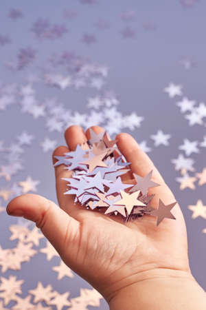 Shiny pink stars confetti in the hands of a small child, Christmas and celebration concept.