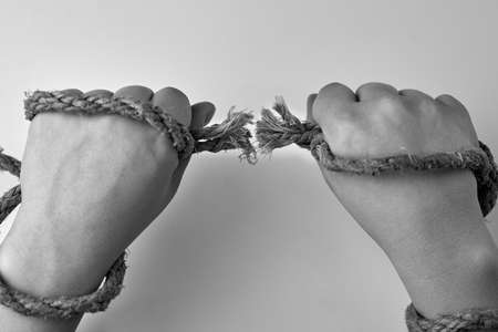 Tearing rope in the hands of a woman, liberation concept, black and white photo. 免版税图像