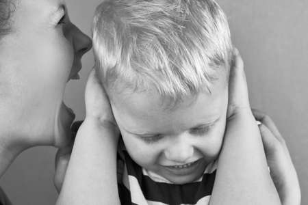 Little boy covers his ears with his hands while angry mom yells at him, black and white photo. 免版税图像