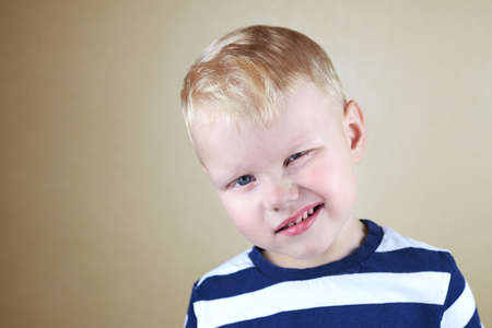 Portrait of a three-year-old caucasian funny boy with a closed eye. 免版税图像