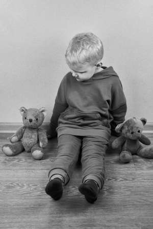 A three-year-old caucasian boy sits alone on the floor next to teddy bears, the theme of child abuse, black and white photo. Banco de Imagens