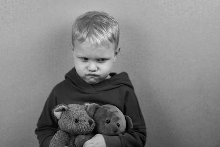 A three-year-old caucasian boy sits alone on the floor and hugs teddy bears, the theme of child abuse, black and white photo.
