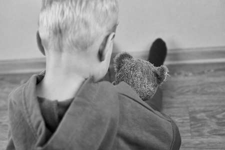 A three-year-old caucasian boy sits alone on the floor and hugs teddy bear, rear view, selective focus, the theme of child abuse, black and white photo. Banco de Imagens
