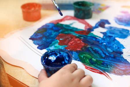 A little boy paints with gouache coloring, leisure and child development. Banco de Imagens