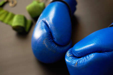 Blue leather boxing gloves, sports bandagesout of focus, close-up.