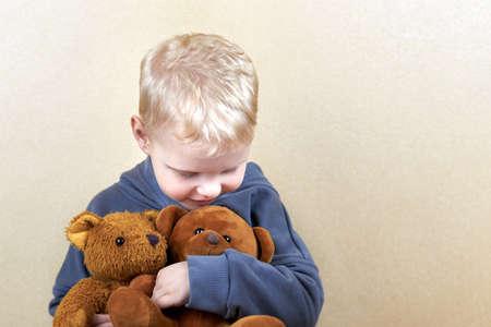 A three-year-old boy hugs two teddy bears tightly.