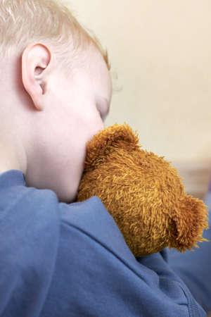 A three-year-old boy kisses and hugs his teddy bear, rear view. Banco de Imagens