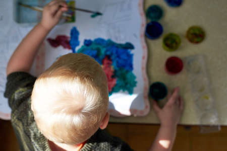 A three-year-old boy paints with gouache coloring, top view, leisure and child development.